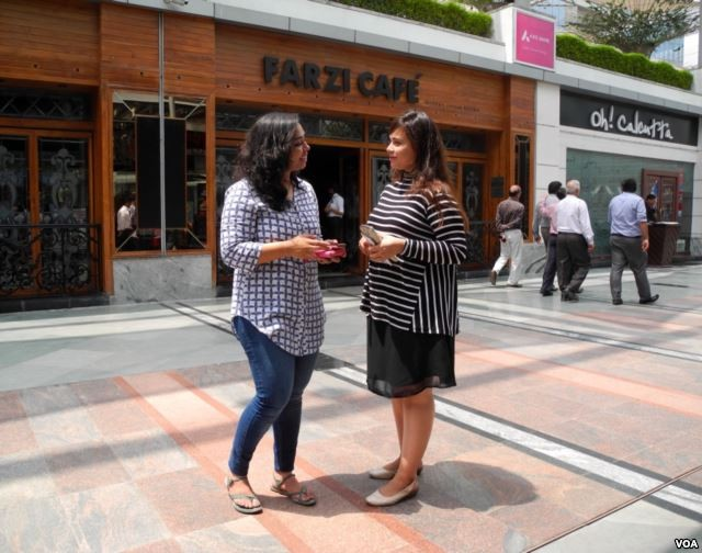 Richa Sharma (left) and Khushboo Gutt (right) enjoy the different experience offered by modern Indian food in restaurants like Farzi cafe. (A. Pasricha/VOA)